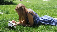 Image of girl reading while laying in the grass.