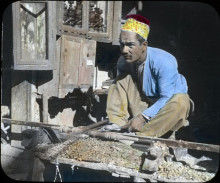 man dressed in a blue shirt and loose yellow pants will yellow hat, crouched over a lathe turning a piece of wood with cabinets in the background