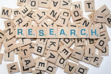 scrabble tiles that spell the word research