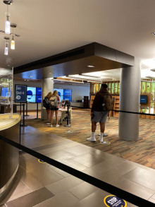 Image of the Shapiro Library Lobby, with a COVID check-in desk and students.