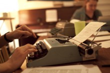 Close-up photograph of someone typing on typewriter