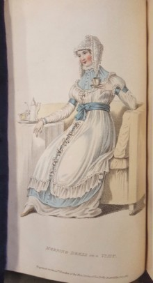 Woman in a blue and white dress siting on a pale yellow sofa, drinking tea