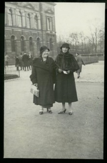 Cornish (left) and Van Volkenburg (right) standing together in winter coats and hats outside, in front of a brick or stone building.