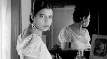 Black and white film still showing a Black woman from the chest up, looking directly at the camera. Also within the frame is the back of her head as shown in a mirror behind her.