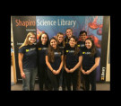Eight students in Library tee-shirts smiling toward the camera