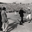 referee shaking hands with university president at football game