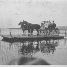 horse and carriage on a ferry crossing a lake
