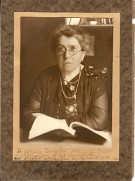 photo of an older Emma Goldman in round glasses, looking at the camera, with an open book in front of her