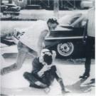 Photo of Tom Hayden sitting on the ground