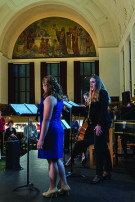 two women facing music stands with an artistic arch in the background
