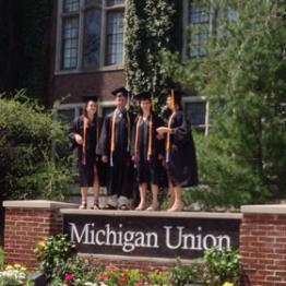 photo of gowned grads in front of the Michigan Union