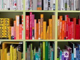 brightly colored design books on bookshelves
