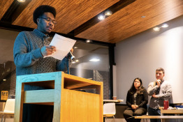 student reading at a podium to an audience