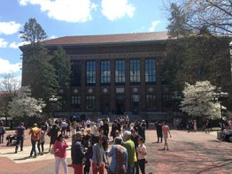 Photo of the front of the Hatcher Library with graduates and parents milling about on the Diag