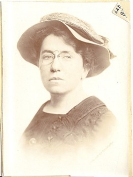 sepia-toned photo of Emma Goldman wearing glasses and a hat