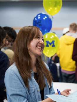 Smiling student with maize and blue balloons in the background