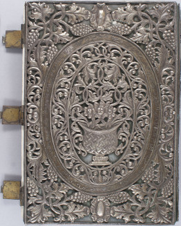 The cover of a 19th century book. The cover is very detailed with silver designs. In the middle is an oval, within the oval is a vase with vines coming out of it. Surrounding the oval is a larger oval full of entwined vines. Outside that, from the outer oval to the edges of the cover, are designs of leaves and bunches of berries. To the left of the cover are three clips. At the top and bottom of each vertical edge, in the middle, is a flower — it looks a little like a sunflower with a large middle & petals.