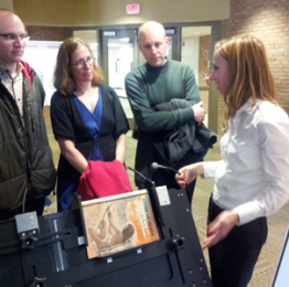 photo of librarians and student next to book scanner