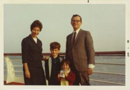 family photo of mom, dad, two young children next to a body of water