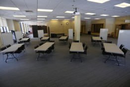 An image of eight tables surrounded by chairs with portable whiteboards near the tables.