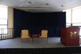 The gallery stage with two chairs, a table and a lectern.