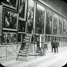 gallery of paintings on the wall with people looking