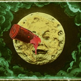 movie still image of face in the moon with a red peg in the eye