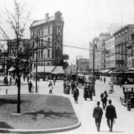 pedestrian intersection with people walking and buildings from early 1900s