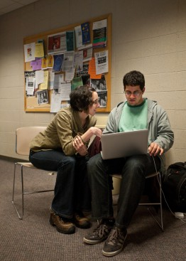 Librarian assisting a student with a laptop.