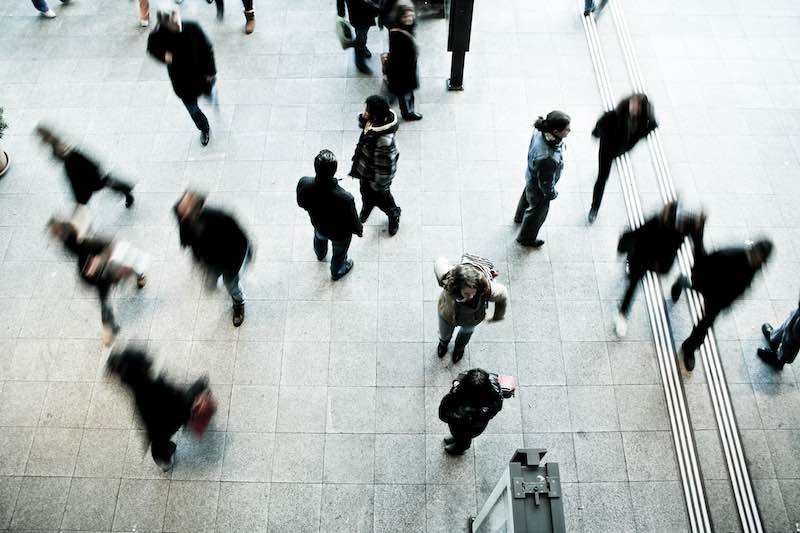 Photo taken above a busy crowd. Some figures are actively walking and their figure is blurred from their movement. Others figures are clear and sharp and they are standing, talking to or watching other people in the crowd.